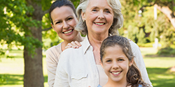 Mother, grandmother, and daughter smiling outdoors