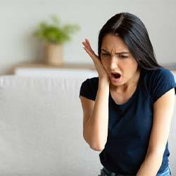 Denton Emergency Dentist woman in pain holding cheek