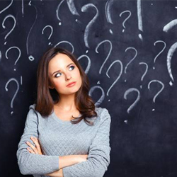 Woman in front of chalkboard surrounded by question marks