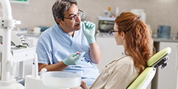 Dentist talking to woman in dental chair