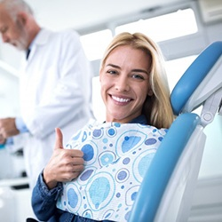 woman giving thumbs up dental chair before receiving nitrous oxide sedation in Denton