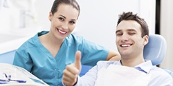 Assistant with patient in dental chair giving thumbs up