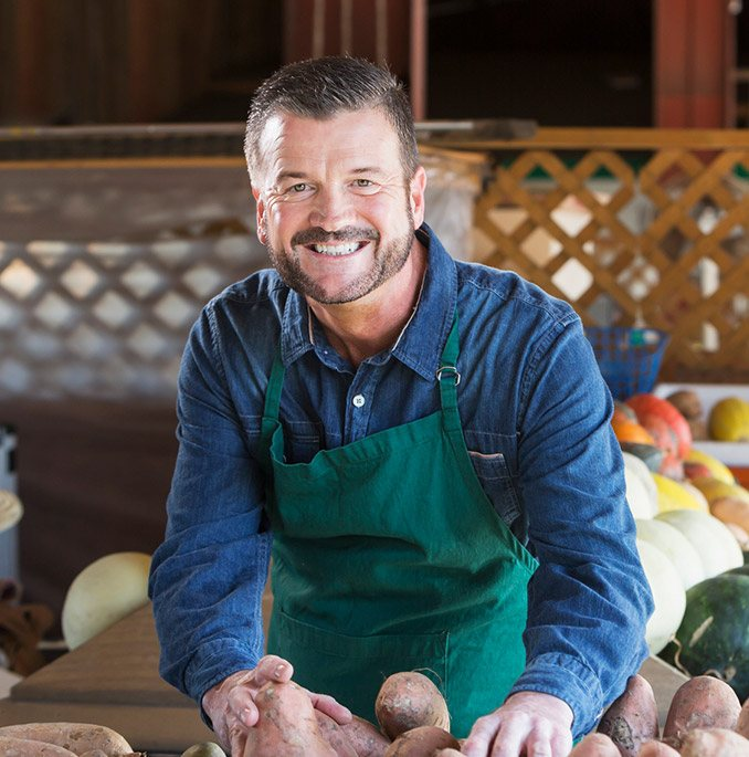 Man wearing apron happily handling potatoes