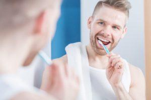 man smiling brushing his teeth
