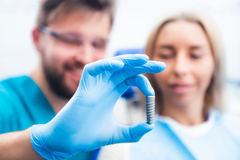 Dentist and patient looking at model of dental implant
