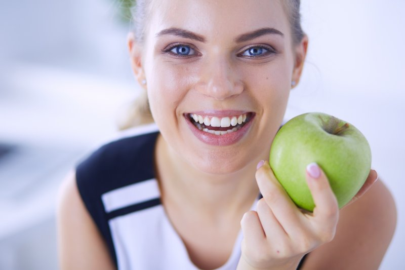 Woman with white teeth smiling while eating an apple