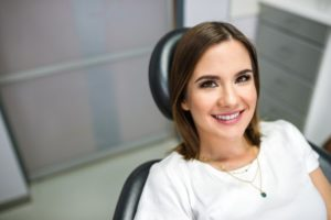 Woman smiling in dental chair while looking at dentist